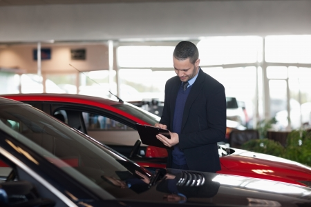 Man writing on a clipboard beside a car in a garage Stock Photo - 16205134