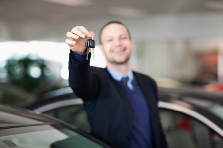Man standing while holding car keys in a dealership Stock Photo - 16204763