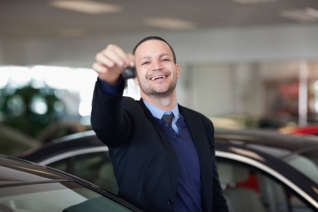 Salesman standing while holding car keys in a dealership Stock Photo - 16205322