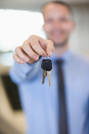 Salesman holding car keys by his fingertips in a dealership Stock Photo - 16205065