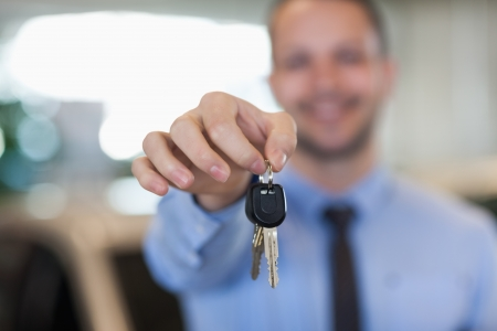 Man holding car keys by his fingertips in a dealership Stock Photo - 16205142