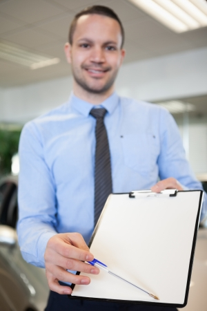 Salesman holding a contract in a dealership Stock Photo - 16203587