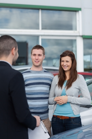 Clients talking with a dealer in a dealership Stock Photo - 16208465