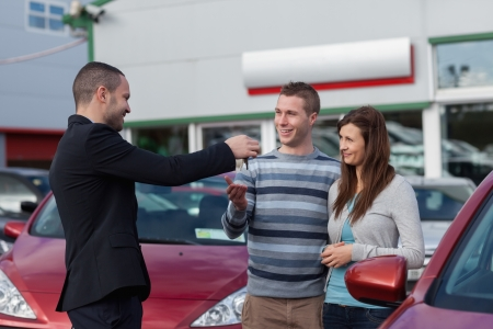 Salesman giving car keys to a couple in a dealership photo