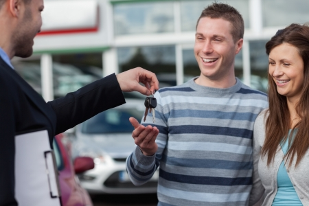 Couple receiving car keys by a dealer in a dealership photo