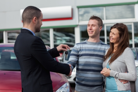 Man shaking hand with salesman in a dealership photo