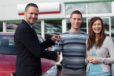Salesman shaking hand of man in a dealership photo