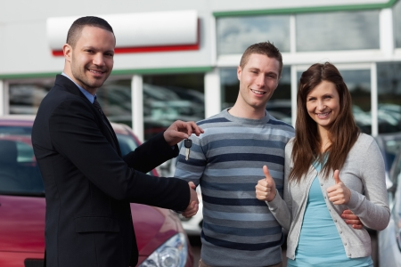 Dealer shaking hand of a man while giving him car keys in a dealership photo
