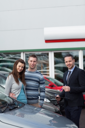 Clients buying a new car in a dealership Stock Photo - 16207024