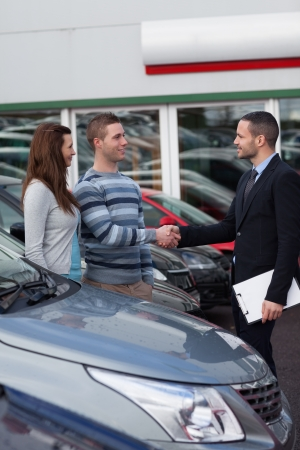 Businessman shaking hand  of a man in a dealership photo