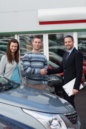 Client shaking the hand of a man in a dealership photo