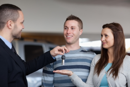 Businessman giving car keys to a woman in a dealership photo