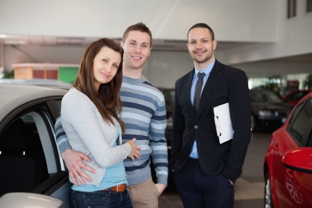 Couple purchasing a car in a dealership Stock Photo - 16207141