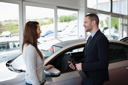 Dealer speaking to a client next to a car photo