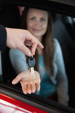 Dealer holding car keys by his fingertips in a dealership photo