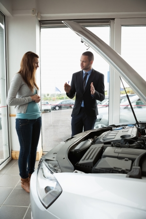 Businessman presenting a car to a woman in a garage photo