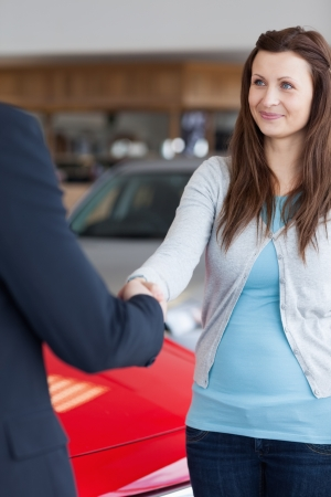 Woman shaking hand to a dealer in a garage photo
