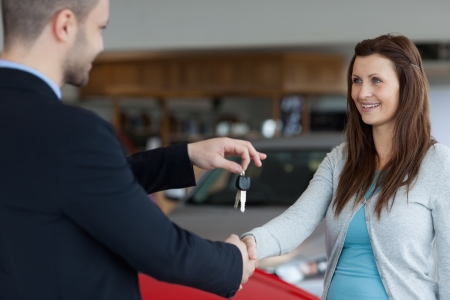 Man giving car keys while shaking hand of a woman in a garage photo