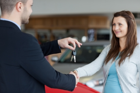 renter: Salesman giving car keys while shaking hand of a woman in a garage