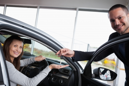 Woman sitting in her car while tending her hand in a garage Stock Photo - 16204544