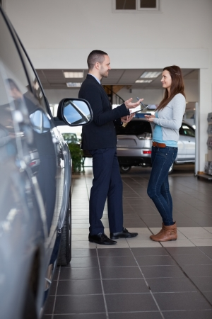 Client speaking with a salesman in a dealership photo