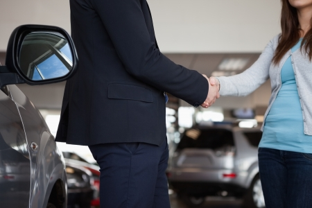Salesman shaking hand of a woman in a garage Stock Photo - 16207582