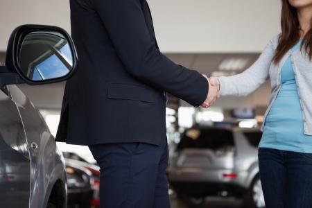 Vendeur secouant la main d'une femme dans un garage
