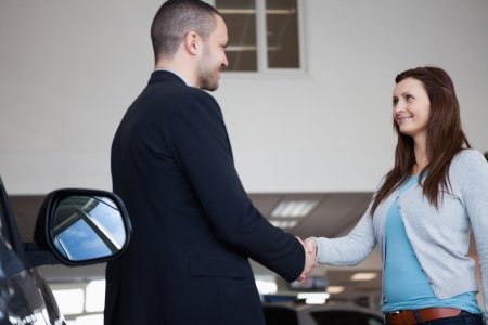 Salesman shaking hand of a client in a garage Stock Photo - 16207058