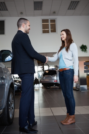 Dealer shaking hand of a woman in a garage Stock Photo - 16208492