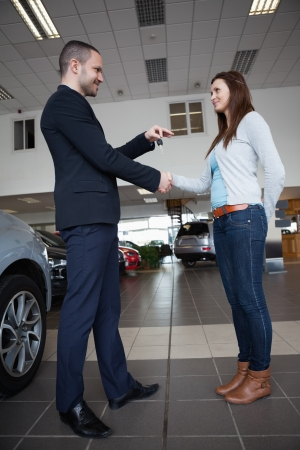 Salesman giving car keys while shaking hand of a client in a garage photo