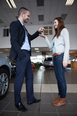 Man giving car keys to a woman in a garage photo