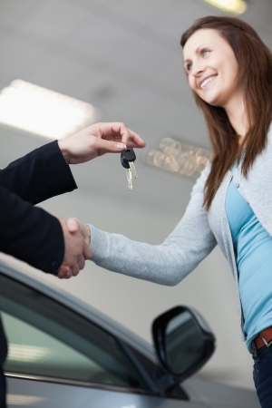 Woman receiving car keys while shaking hand in a garage photo