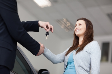 Client receiving keys car while shaking hand  in a garage photo