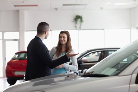 Dealer speaking to a woman in a dealership Stock Photo - 16203160