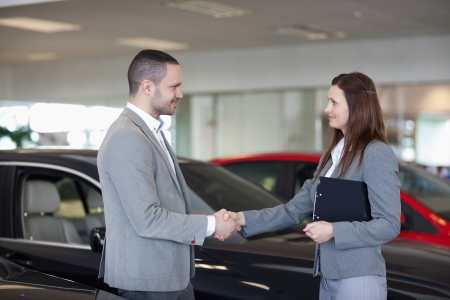 Businesswoman shaking hand of a man in a dealership photo