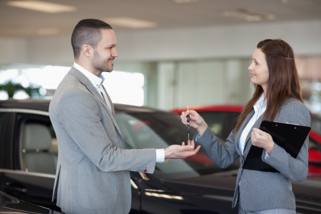 Woman giving car keys to a client in a dealership Stock Photo - 16207747
