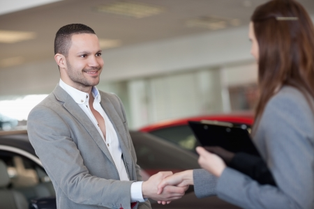 Businesswoman shaking hand of a client in a dealership photo