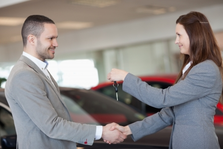 Man receiving car keys while shaking hand in a dealership photo