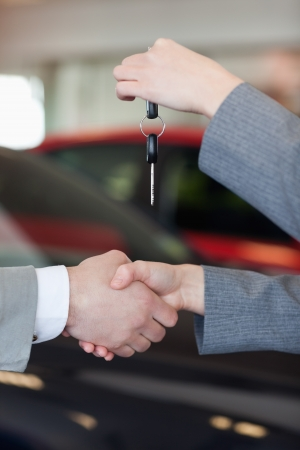 Close up of a woman giving car keys to a man in a dealership Stock Photo - 16207863