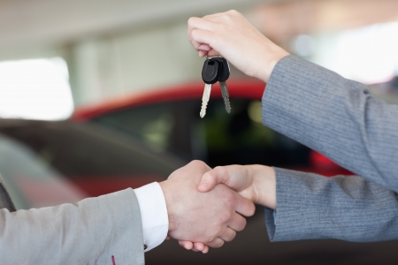 Close up of a woman shaking hand to a man in a dealership photo