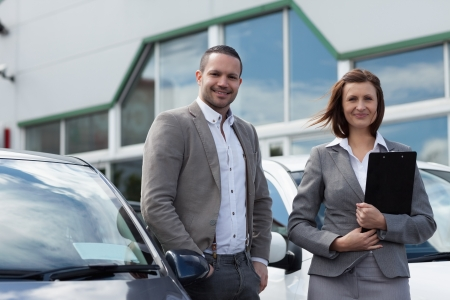car dealer: Man buying a new car in a garage Stock Photo