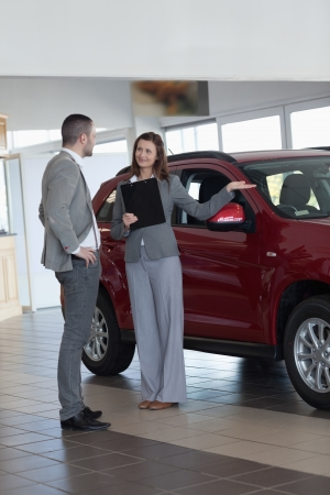 Businesswoman showing a car in a dealership photo