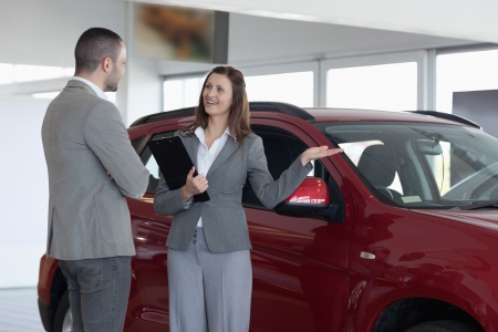 Businesswoman showing a car to a client in a dealership Stock Photo - 16205025