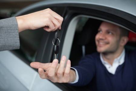 Man receiving car keys while sitting in his car in a garage Stock Photo - 16204590