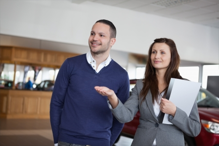 Woman showing something to a man in a dealership Stock Photo - 16208266