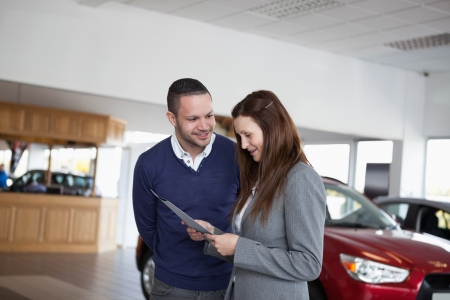 Woman reading a folder in a dealership Stock Photo - 16207593