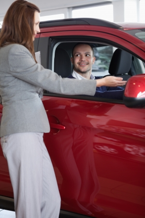 Businesswoman showing something to a man in a dealership photo