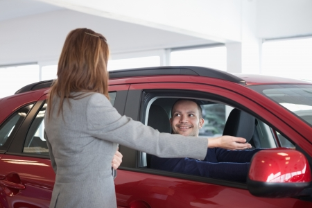 Businesswoman presenting something to a man in a dealership photo