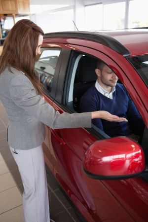 Woman presenting something to a client in a dealership photo
