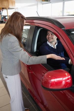 Businesswoman presenting the car to a client in a dealership photo